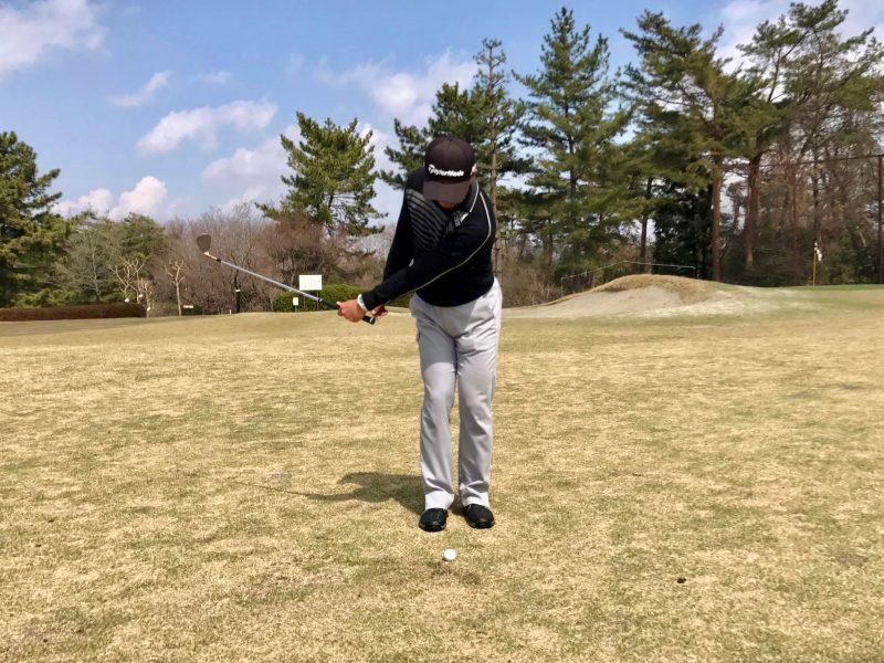 ゴルフアプローチショット左腕一本テークバック正面の写真