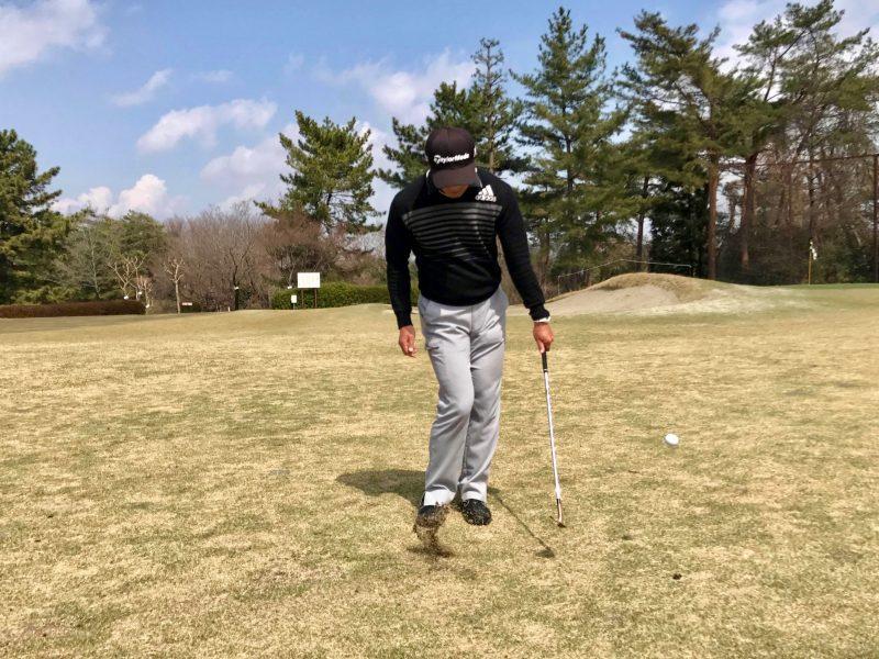 ゴルフアプローチショット左腕一本インパクト正面の写真