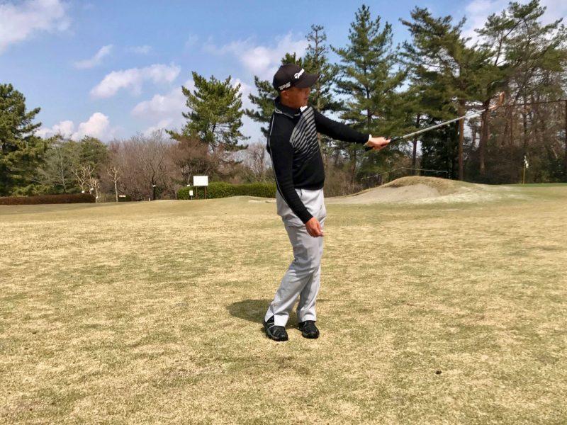 ゴルフアプローチショット左腕一本フィニッシュ正面の写真