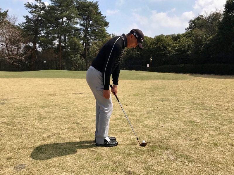 ゴルフアプローチショット左腕一本アドレス飛球線後方からの写真