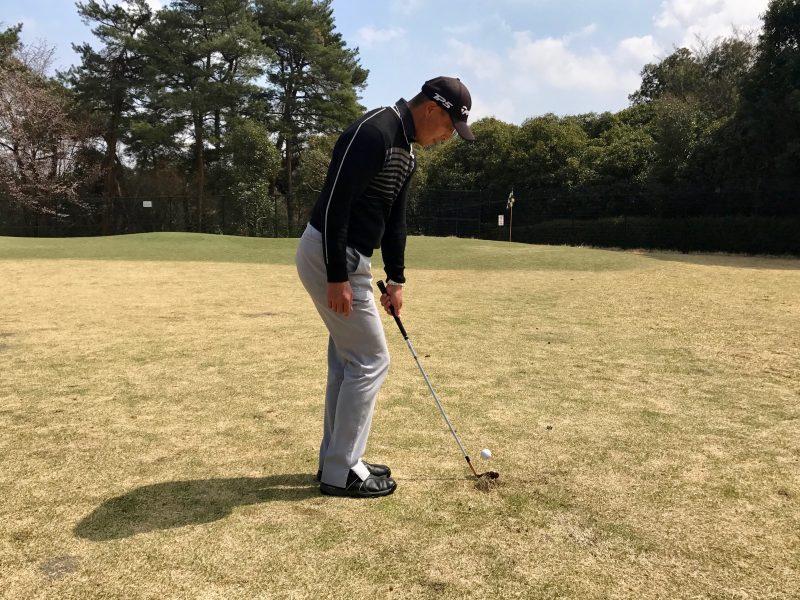ゴルフアプローチショット左腕一本インパクト飛球線後方からの写真