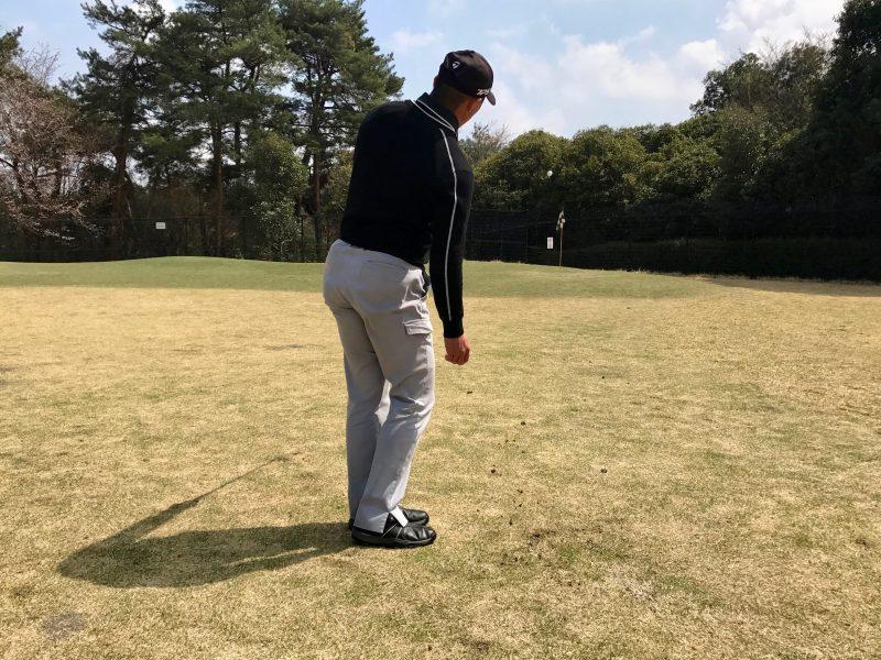 ゴルフアプローチショット左腕一本フィニッシュ飛球線後方からの写真