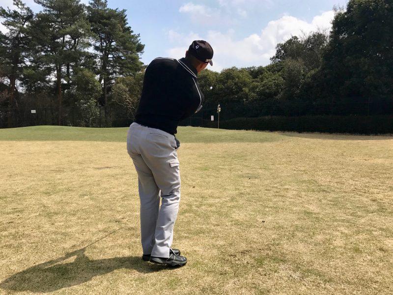 ゴルフアプローチショットフィニッシュ飛球線後方からの写真