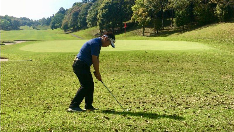 GEN-TENゴルフコースレッスン左足下がりアプローチ右脚を引いたアドレス飛球線後方からの写真