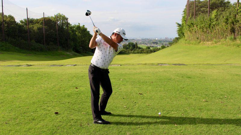 GEN-TENゴルフコースレッスンドライバーショットトップオブスイング膝が伸びた状態飛球線後方からの写真