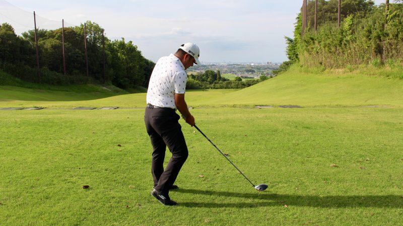 GEN-TENゴルフコースレッスンドライバーショットインパクト膝が前に出た状態飛球線後方からの写真